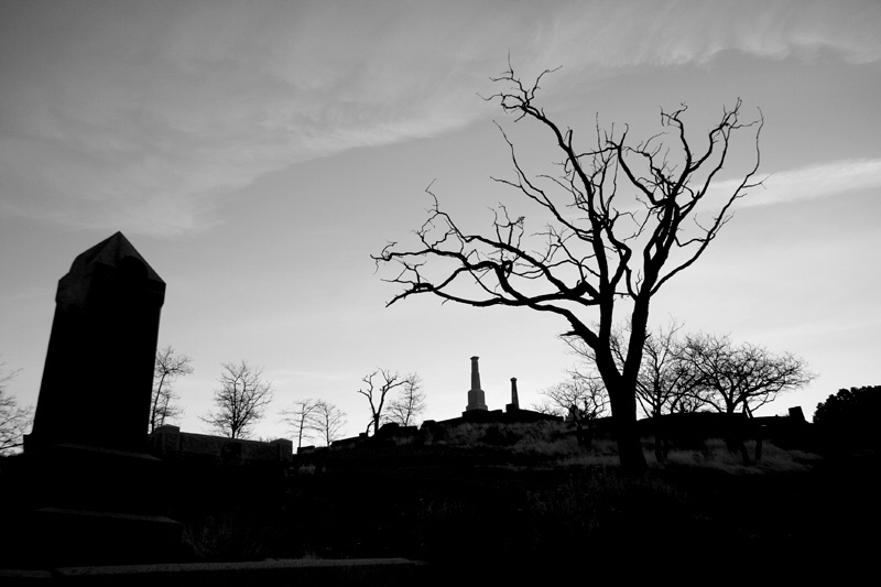 A black and white photo of a graveyard at dusk.